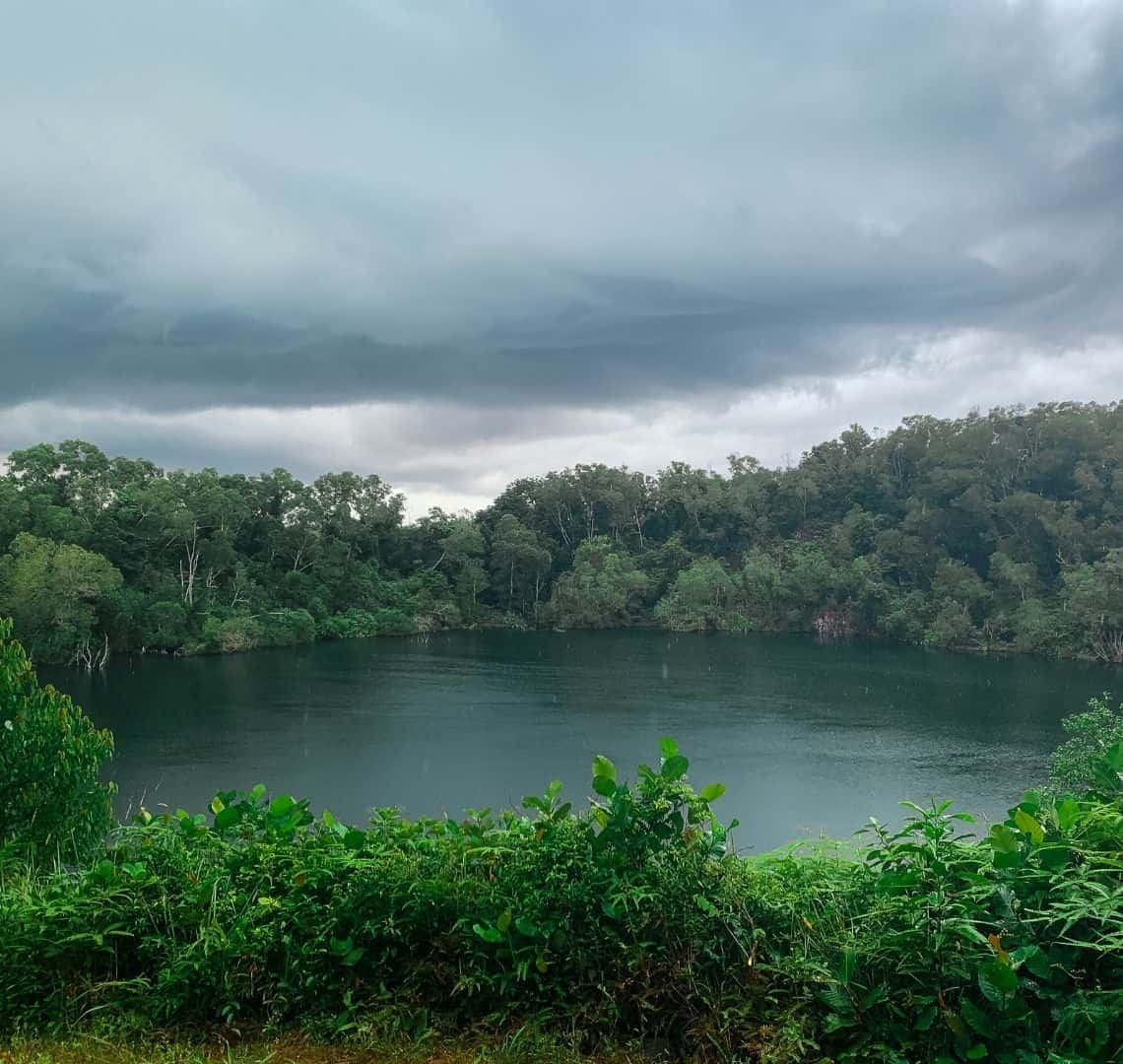 Bright green foliage at the bottom gives way to the dark water in teh quarry. It is surrounded by trees. The sky has dark storm clouds.