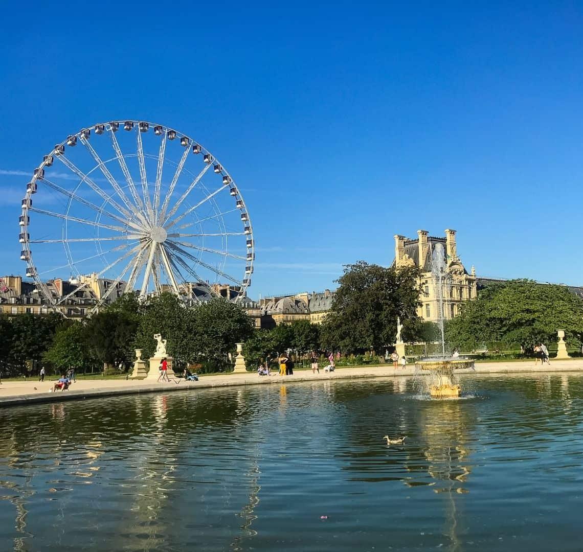 There is a large pond taking up the bottom half gf the page with a lone duck swimming in it. Behind is is a gravel path and some statues. Behind them is a wall of trees. Towering above the trees is the Paris wheel and a large cream building. The sky is bright blue with no clouds.