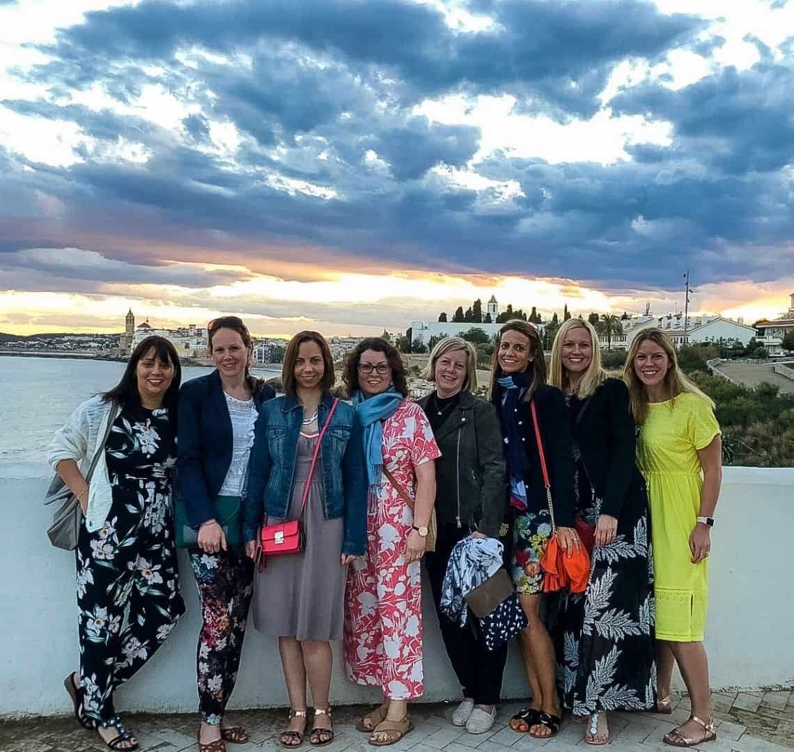 There are eight ladies stood in front of a white wall. We are all dressed for dinner adn wearingg flat shoes for walking around beforehand. Behind is there are clouds in teh sky that are dark from the coming night. The sky on the horizon is a watery pastel pink and orange.