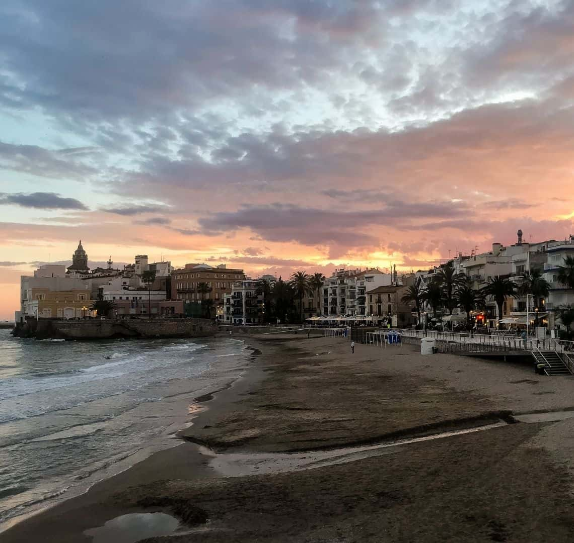 Sitges Beach has dark sand taking up around one half of the bottom of the photo. The sea, on the left, has gentle waves with white foam contrasting against the dark waters. On the right are the white paving stones of the promenade and a white railing, behind which some shops and restaurants are just opening. The headland is in the middle left and shows more old Spanish buildings. The sky is a myriad of pastels with the brightest yellow, but still muted, where the sun had been. There are some clouds in teh sky which is turning a deeper blue at the top of the image.