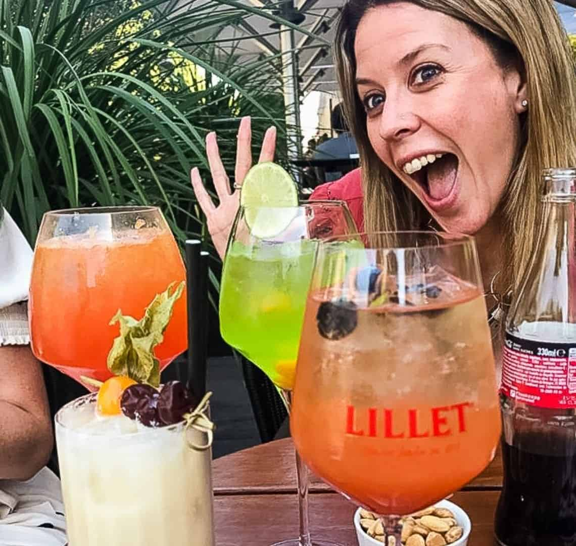 There are four drinks on the table, two are orange aperol sprites, between them, one is a bright green concoction with a slice of lim wedges onto the side of the galss, in the foreground, there is a creamy white drink in a tall glass with some fruit on a little skewer balanced on the top. I am in the background smiling with my mouth wide open and my hand splayed, palm towards the camera. Behind me is some green foliage.