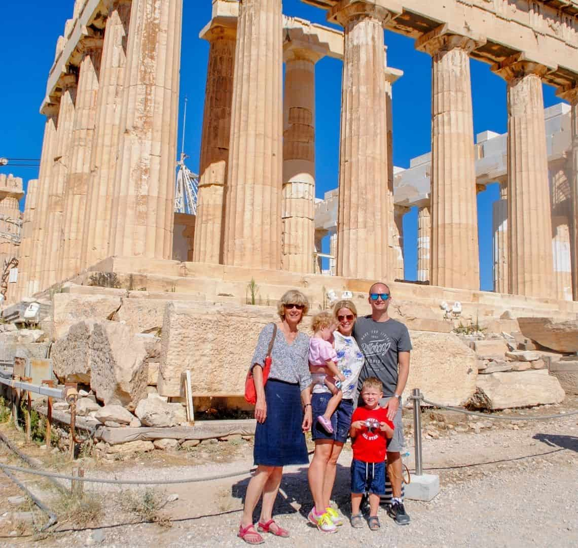 All of us in front of the Parthenon in Athens. Granny Wanderlust is in a flowery top and a blue skirt, I am wearing a white flowery top and blue shorts, carrying Thing 2 in a pink t-shirt. Next t one is Mr Wanderlust in a grey t-shirt and grey shots. Thing 1 is in front of us wearing a bright red t-shirt and blue shorts. The sky is bright blue and can be seen through the pillars of the Parthenon.