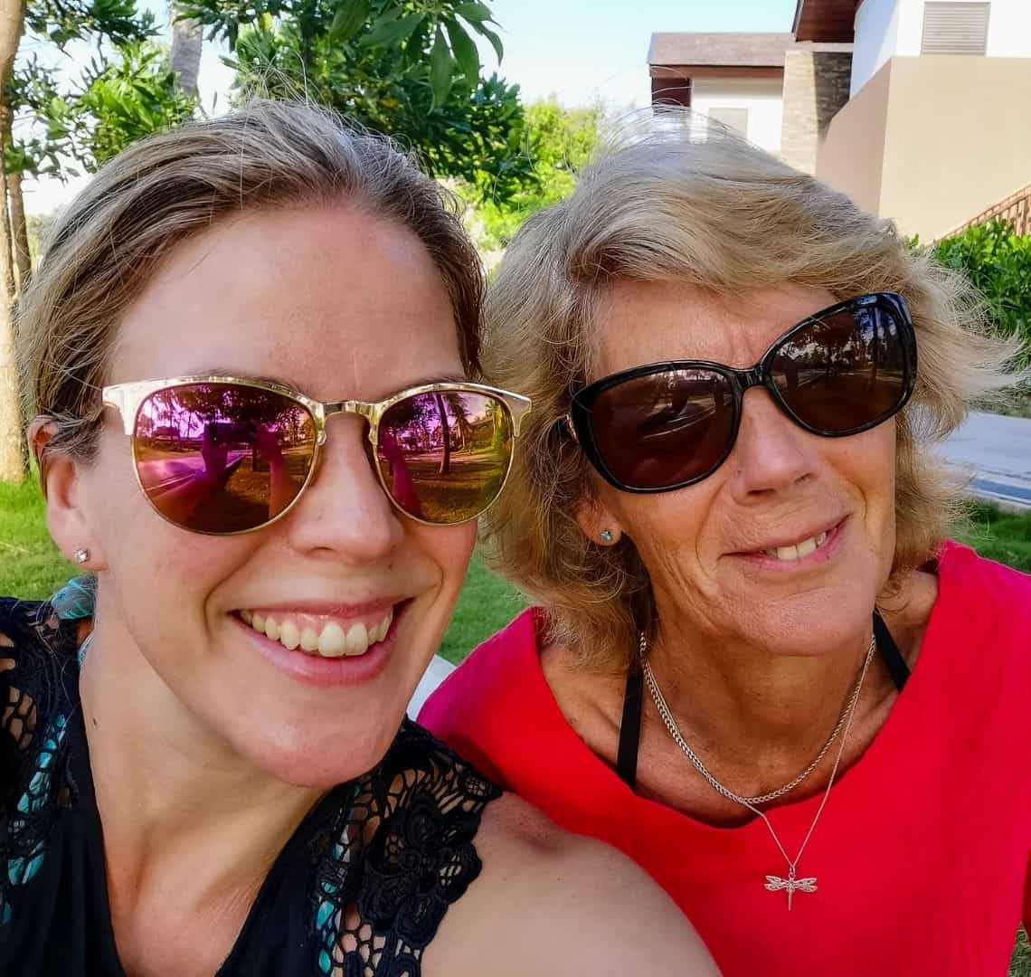 Me and Granny wanderlust selfie. We are both wearing sunglasses. We have swimsuits on under our tops - mine is black and hers is red. Behind us are a few trees, some blue sky and a path.