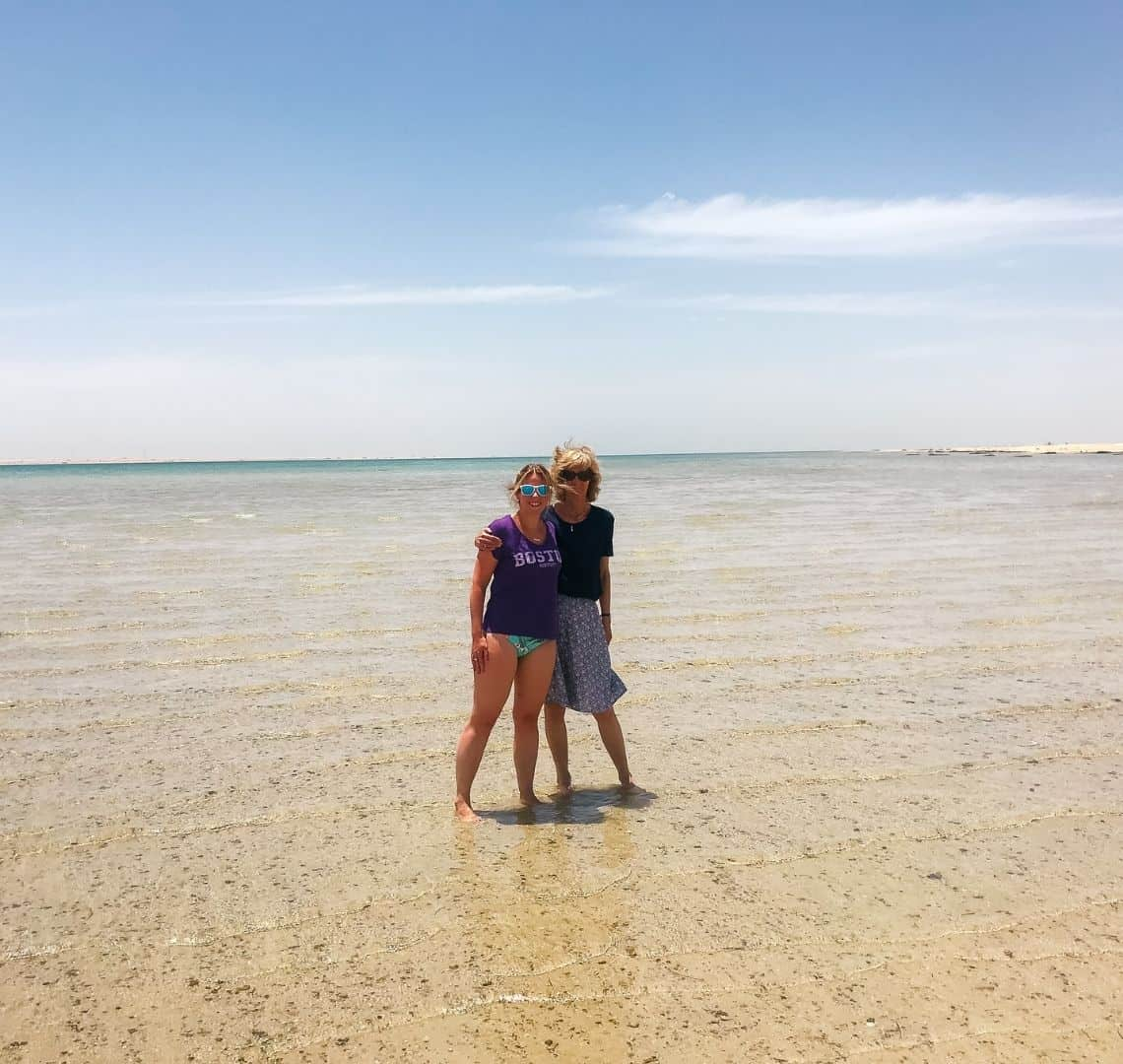 Me and Granny wanderlust are standing in crystal clear water. It is so clear, it is the colour of the sand at the bottom. In the distance is gets blue. The sky is blue with some wispy clouds. She has her arm around me.