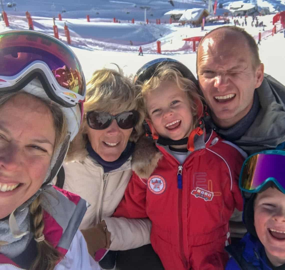 Ski selfie! We are all wearing ski and winter wear. It is me with goggles on my helmet, Granny wanderlust wearingg a cream coat and sunglasses, Thing 2 in a red ski suit, Mr Wanderlust squinting in a grey jacket and Thing one in a blue jacked and with blue goggles on his helmet (partially cut off). Behind us is snow and other skiers