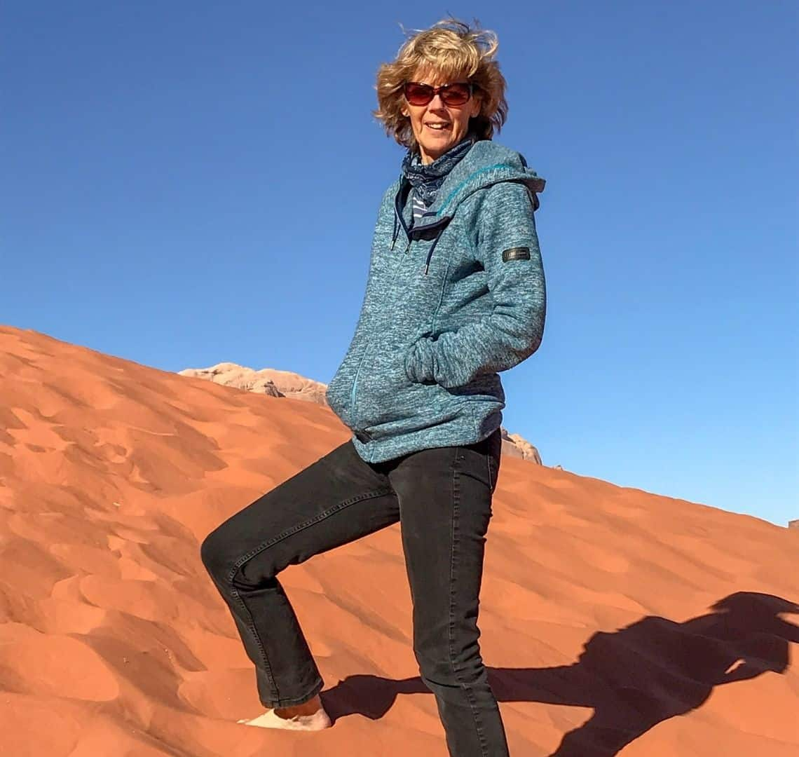 Granny wanderlust on a red sand dune. Behind her the sky is bright blue. She has black trousers on and a blue jumper. Her hands are in her pockets and her right leg is bent, a pace up the dune. She has sunglasses on and her hair is windswept.