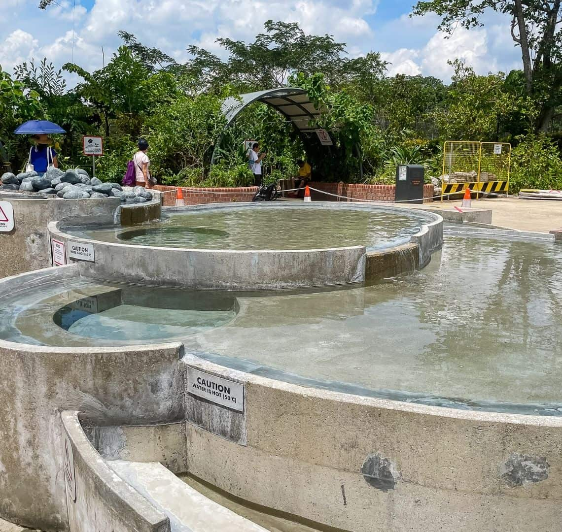 The image shows the cascading pools in Sembawang, They are circular and made of concrete. The water is clear. Behind the pools is a trellis that provides shade over some seats that are in front of a red brick wall and some tropical green plants. In the mid ground there are four people walking and sitting.