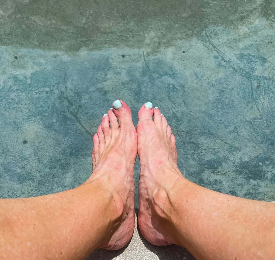 My legs and feet hovering above the clear water and grey concrete