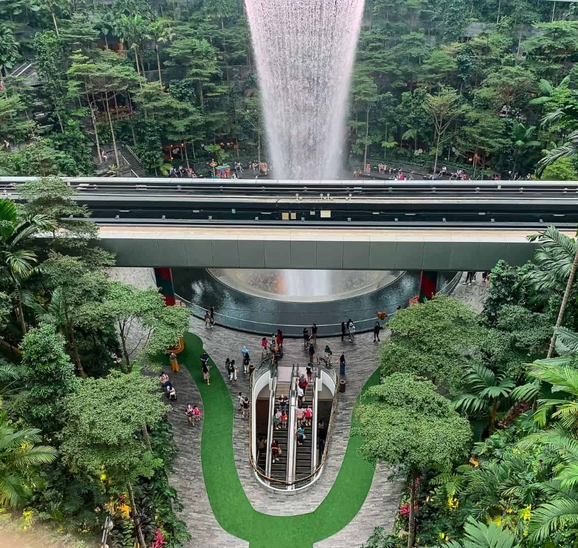 """Changi Airport's rain vortex - clear water cascades from the ceiling to several floors below. The """"rainforest"""" area is full of lush green tropical plants all built around the circular vortex. Several people are milling about on the paved floor. There is an escalator going down in the middle of the picture at the bottom and a railway running horizontally through the middle."""