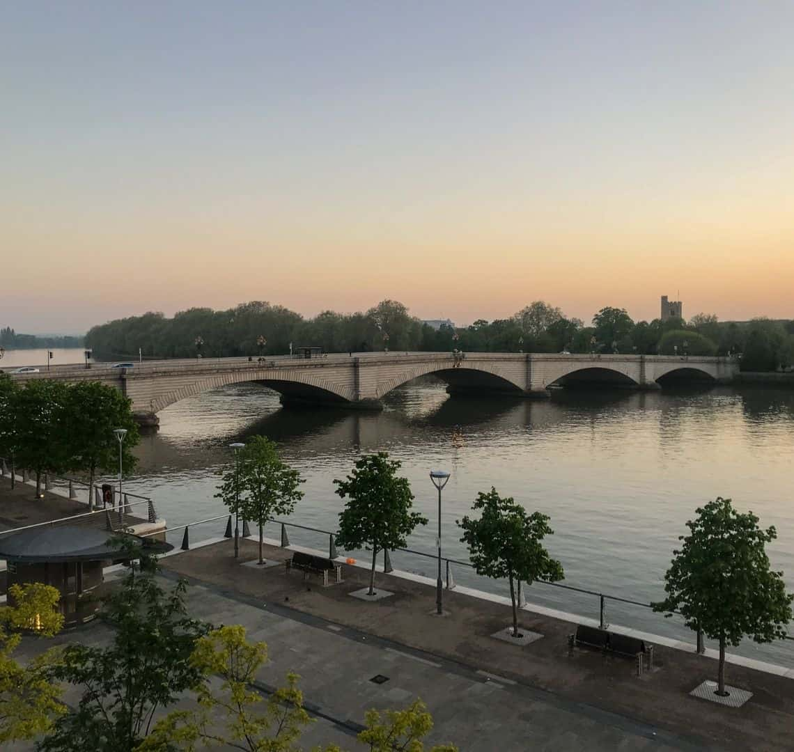 The sun is setting and teh sky is a variety of pastel oranges and pinks behind Putney Bridge with the tide in. There are some trees and benches on the pathway in the foreground