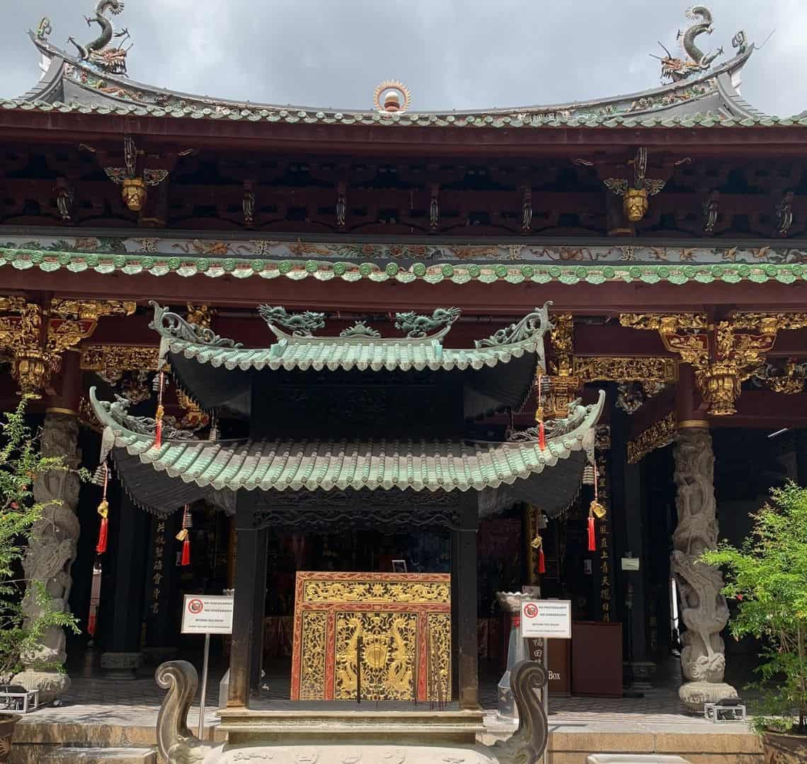 Thing Hock Keng Temple from the front with oxidised Chinese roof, ornate carved pillars and gold left on the beams