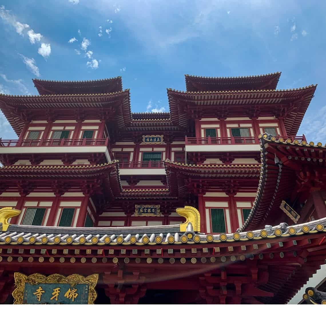Buddha Tooth Relic Temple has Chinese roofs, white walls and lots of red edging with green shutters on the windows. above it the sky is blue with just a few clouds in the sky.