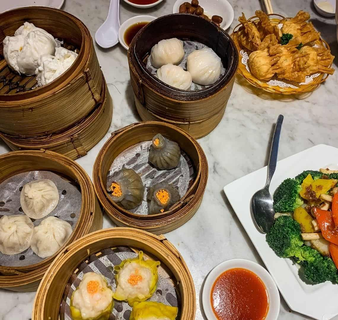 A selection of dumplings in bamboo steamers on a marble tabletop. On the bottom right is also a selection of colourful stir fried vegetables and at the top righter some fried wantons