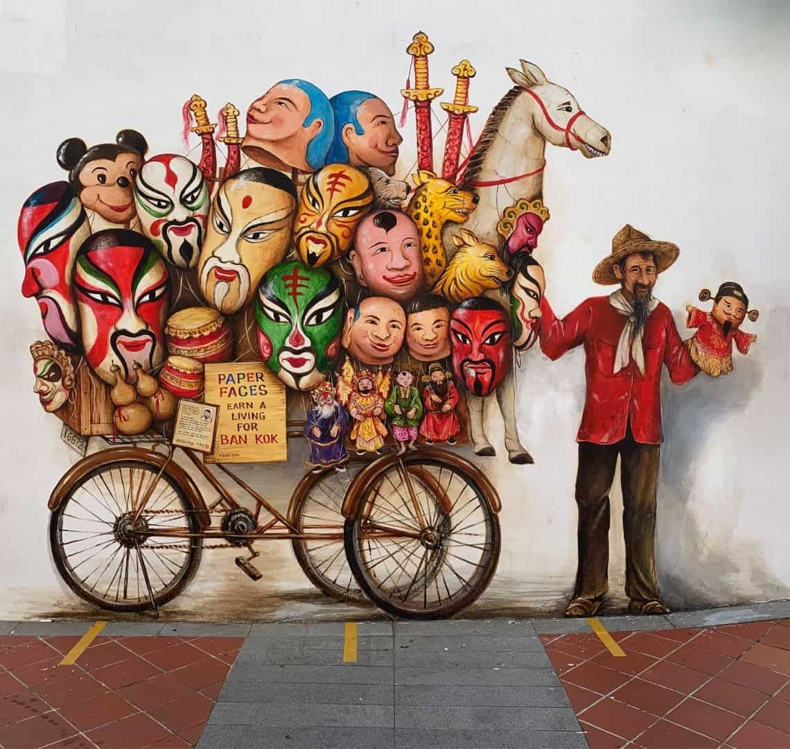 Painted on a white wall in Chinatown Singapore is an image by Yip Yew Chong of a hawker in a red shirt with a white scarf and brown trousers and a hat. In his left hand is a puppet and his right hand is holding up a bicycle that is loaded with puppets, face masks, swords and a toy horse.