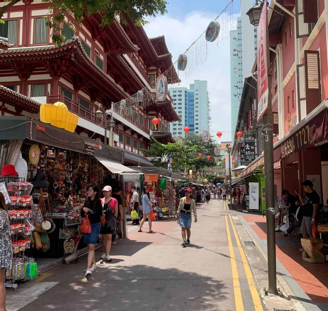 A Comprehensive Guide to Chinatown Singapore - Street view of some stalls along a street in Chinatown. They are selling all manner of tourist tat and there are a few tourists on the street. On the upper left above the stalls are the red walls of Buddha Tooth Relic Temple with its Chinese style roofs.