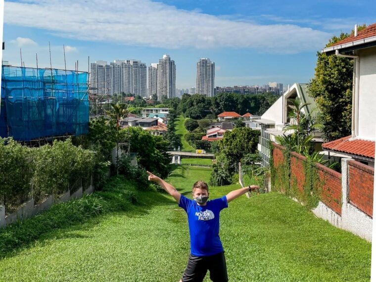 Think one in great shorts and a bright blue top stands at teh top of a green stretch of grass. On the left is green shrubbery and on teh rights some white walls with Spanish style terracotta grooves and shutters. There is also some scaffolding on the left. In the distance is a high rise, some smaller buildings and a blue sky