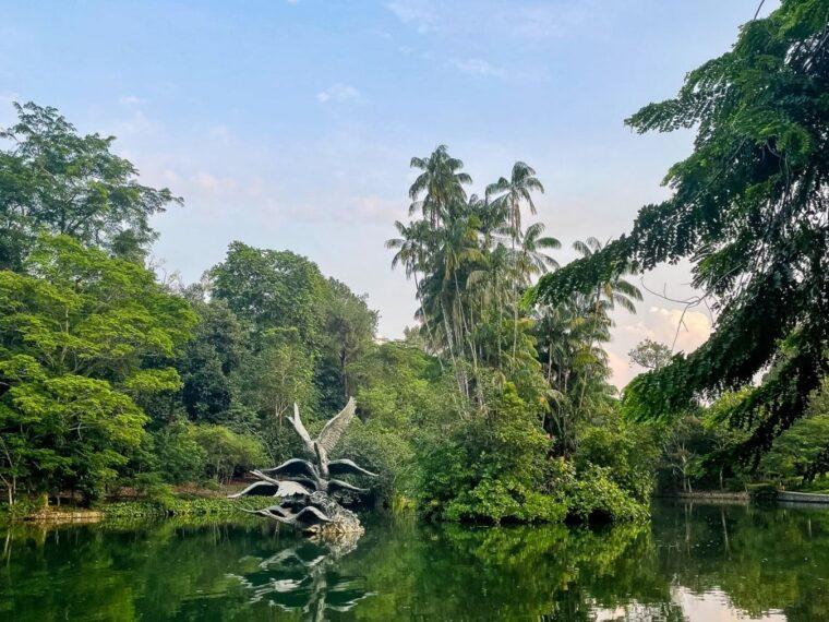 The happiest day in the world - the statue of three swans in teh middle of the still lake are reflected almost perfectly. There are lots of green trees that surround it and the sky is pastel blue with a hint of a sunrise starting