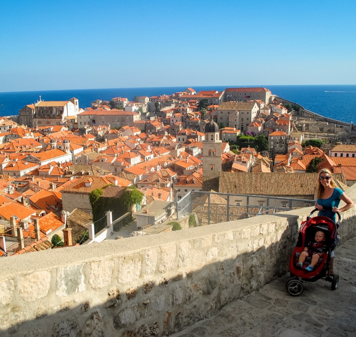 Best family holiday destinations - me with Thing 1 in a pushchair on the Dubrovnik Old Walls with old town Dubrovnik and the sea in the background