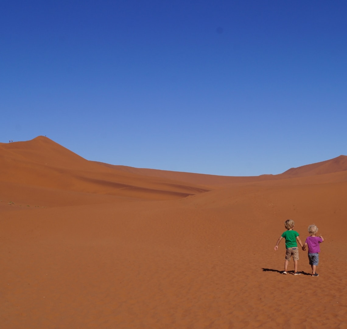 Best family holiday destinations - Travelynn Family's 2 sons exploring the Namibian red sand dunes