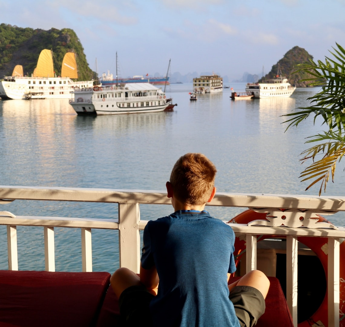 Best family holiday destinations - Go Live Young's son looking out over the cruise ferries and dramatic landscape of Ha Long Bay
