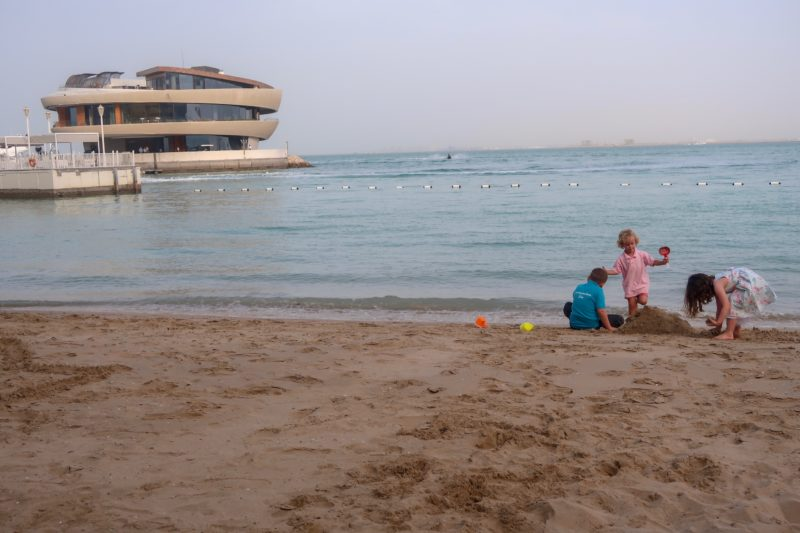 Four Seasons Doha - the Things and a friend building a sandcastle on the beach with Nobu in the background