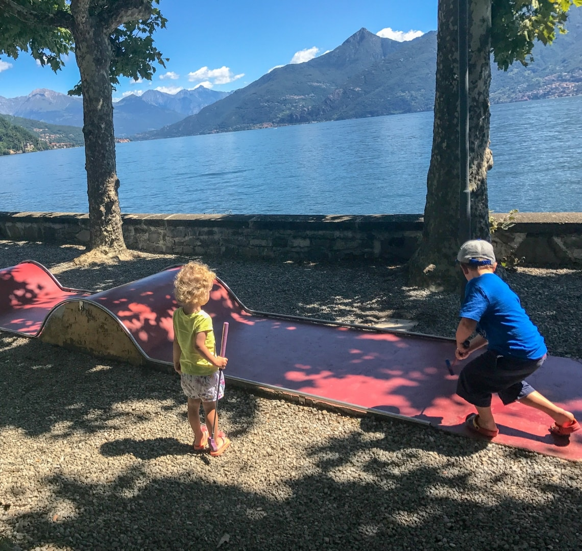 How to have an epic family holiday - the Things playing mini golf in Lake Como Italy with the beautiful lakes and mountains in the background