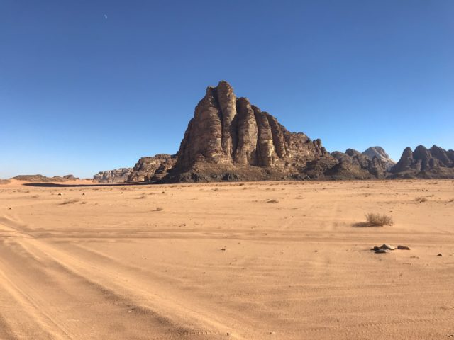 The sandstone rocks just loom straight out of the desert sand