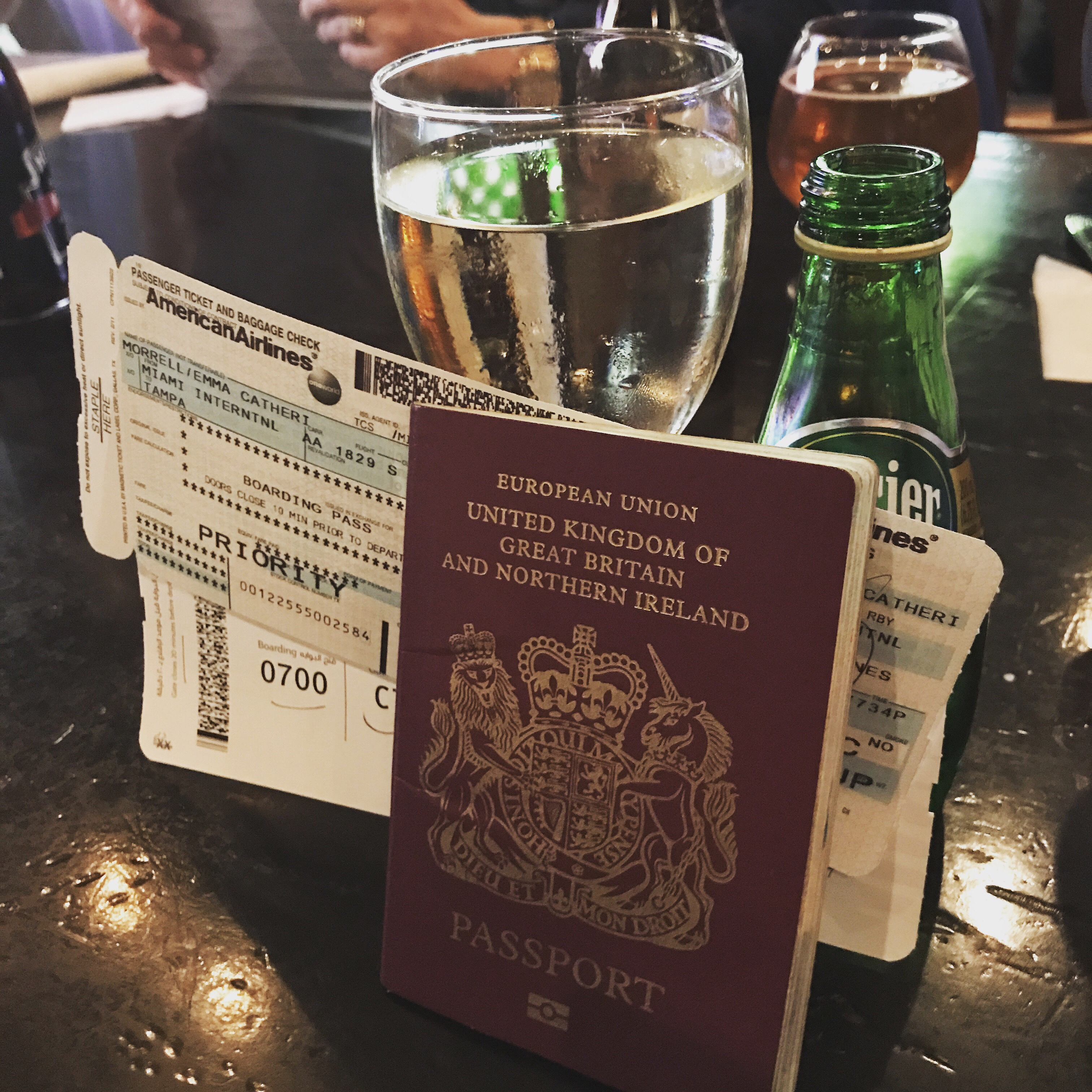 Passport, boarding card, glass of wine and water